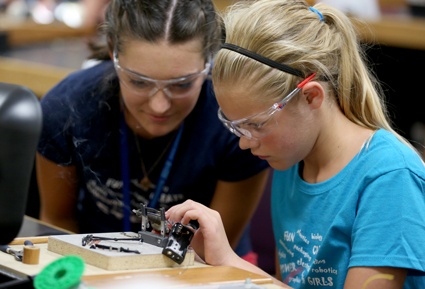 A high school lab assistant, left, watches as a STEPs for Girls participant wires a battery harness for her robot. To make the harness, girls cut, stripped and soldered the wires.