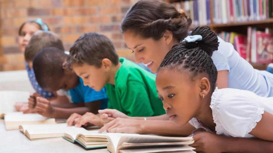 A Teacher assisting her students reading.