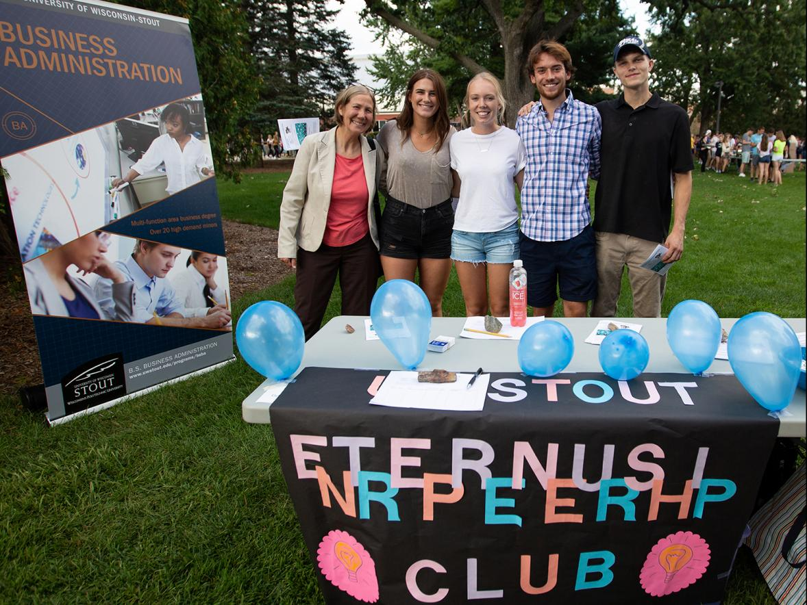 From left, Assistant Professor Mary Spaeth, Megan Nimsgern, Kayla Bolster and other members of the Entrepreneurship Club gather at the Backyard Bash student event on campus in September.
