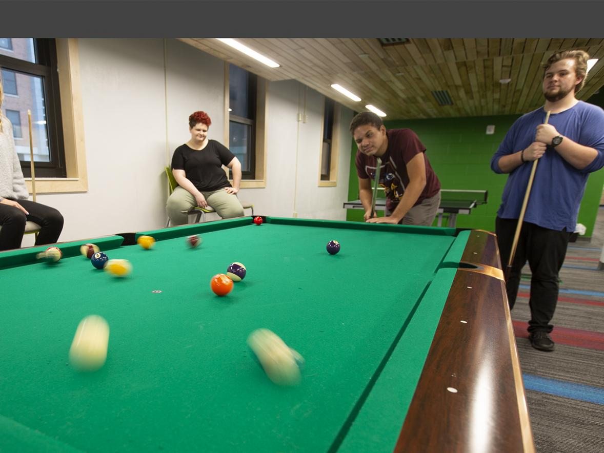 Students play a game of pool at UW-Stout's North Hall.The residence hall has earned incentives for its energy savings.