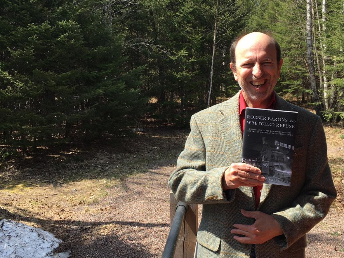 "Robert Zeidel, UW-Stout professor and interim dean of the College of Arts, Communication, Humanities and Social Sciences, with his book ""Robber Barons and Wretched Refuse: Ethnic and Class Dynamics During the Era of American Industrialization."""