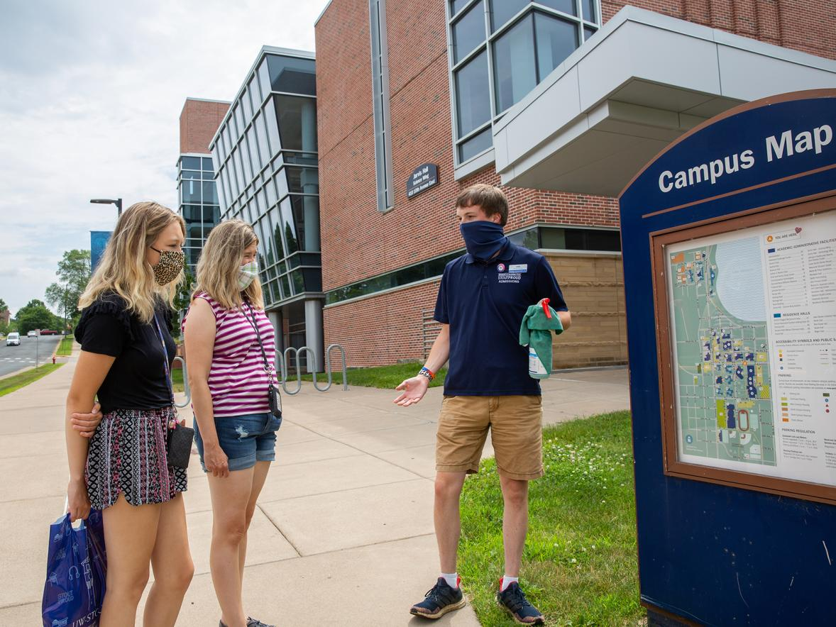 An Admissions Office guide wears a mask and carries sanitizer spray while conducting a tour for new students at UW-Stout.