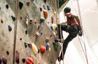Student scaling the climbing wall.