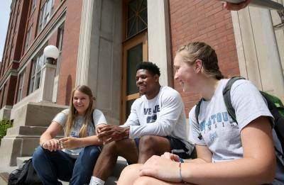 Students sitting and chatting in front of Harvey Hall.