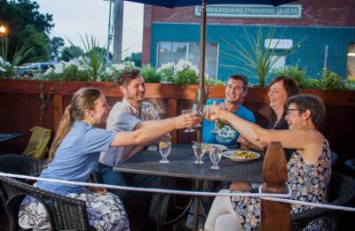 A group of friends cheers while enjoying a cold beer at a local restaurant.