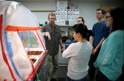 "Associate Professor Matt Kuchta, left, talks with students about the Martianlike ""Hab,"" or habitat, he has created in his lab."