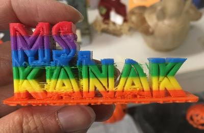 3D printed name: Ms. Kanak, in rainbow letters.